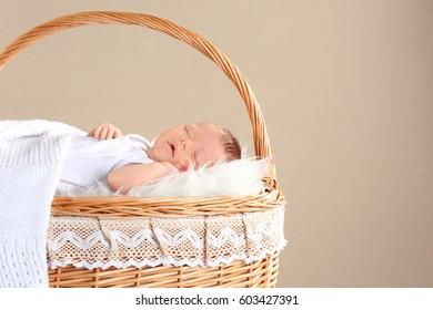 Cute little baby sleeping in wicker basket on color background