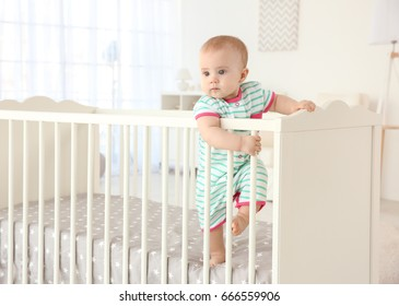 Cute little baby standing in crib at home