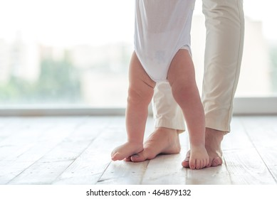 Cute little baby is toddling while learning to walk, mom is holding his hands, cropped
