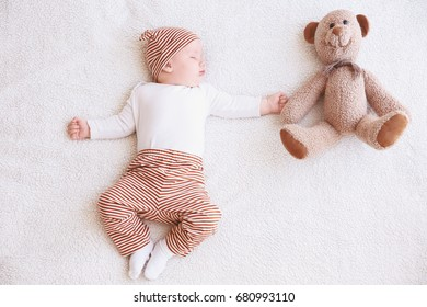 Cute little baby with toy bear sleeping on plaid at home