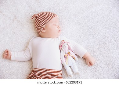Cute little baby with toy bunny sleeping on plaid at home