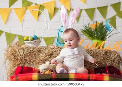 Cute little baby wearing bunny ears sitting near Easter decorations with chicken