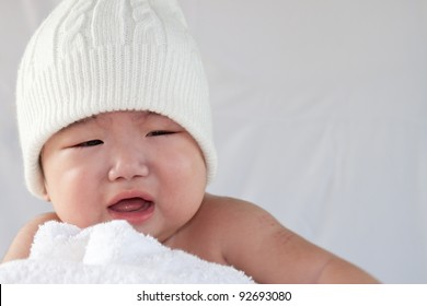 A cute little baby is wearing a white hat. The baby could be a boy or girl and has brown eyes. use it for a parenting or love concept