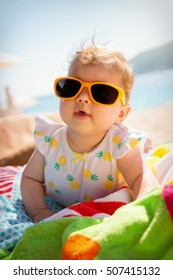 Cute little baby wearing yellow sunglasses and enjoying time on the beach.