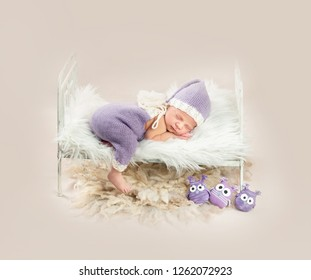 Cute little baby in white and purple knitted suit sweetly sleeping in small bed