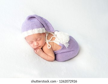 Cute little baby in white and purple knitted suit sweetly sleeping on white blanket