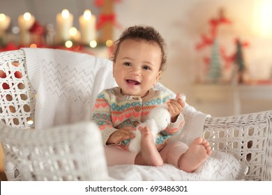 Cute little baby in wicker chair on blurred background