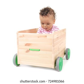 Cute little baby in wooden cart, isolated on white