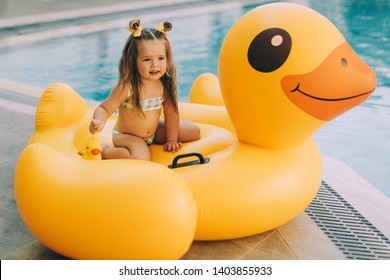 Cute little baby-girl with long hair holding a yellow duck. In the background is an inflatable swimming duck and a pool with blue water. The concept of children's summer holidays and resort hotel