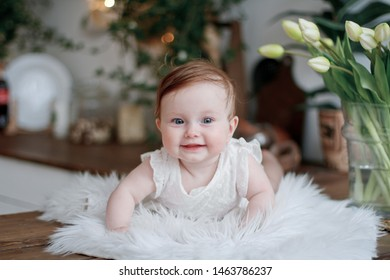 cute little baby-girl smail   with blue eyes in white clothes crawling on the rug in a beautiful interior against the background of flowers