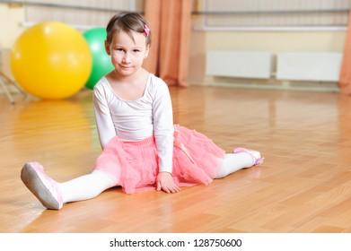 Cute little balerina stretching on floor in gymnasium