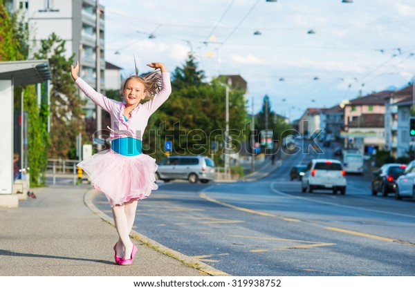 Cute little ballerina girl outdoors, wearing dance clothes, dancing in the street