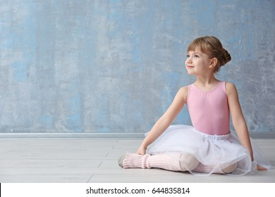 Cute little ballerina sitting on floor in dance studio