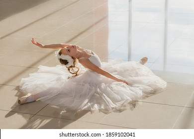 Cute little ballerina in white ballet costume and pointe shoes is posing on floor.  Child girl is studying ballet. Kid and dance. Copyspace.