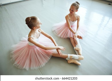 "Cute little ballerinas in pink costume and point shoes is sitting on the floor. Kids in dance class. Child girl is studying ballet in pink skirt. Two little ballet girls sit in ""dying swan"" pose"