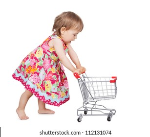 Cute little barefoot girl in a colourful dress pushing a miniature wire shopping trolley isolated on white
