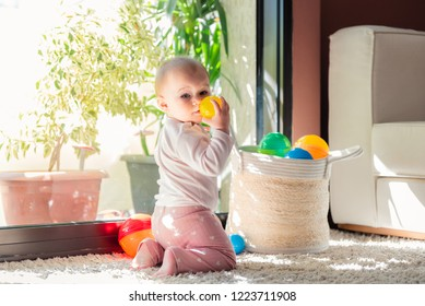 Cute little beautiful baby girl playing with small colorful plastic balls on living room carpet.