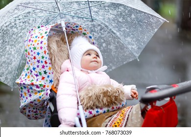 Cute little beautiful baby girl sitting in the pram or stroller on cold day with sleet, rain and snow. Happy smiling child in warm clothes, fashion stylish baby coat. Baby with big umbrella