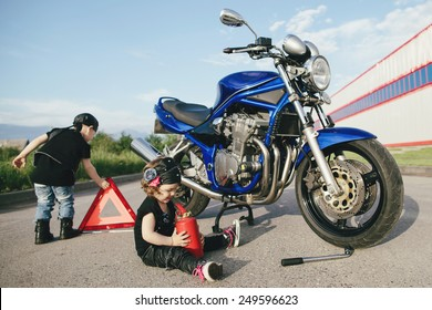 cute little bikers repairs motorcycle on road