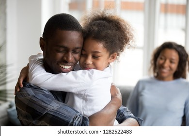 Cute little black girl embracing happy african american dad at home, mixed race kid daughter and father hugging cuddling, daddy and child love care connection good relations concept, family reunion