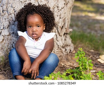 Cute little black girl sitting infront of a tree with a serious expression on her face.