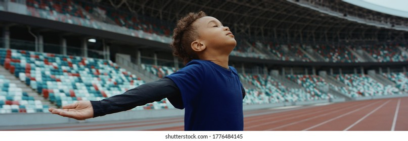 Cute little black kid boy spreading his hands on an empty stadium, dreaming of becoming professional player, soccer star