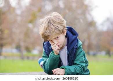 Cute little blond boy acting angry in a park