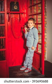 Cute little blond boy in a grey suit  call on the telephone in a retro British telephone box. Boy with an old telephone in the red phone booth in the English style. Child with a black handset.