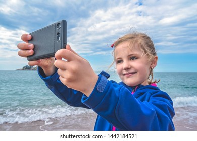 Cute little blond Caucasian girl taking selfie with mobile phone on the beach in autumn