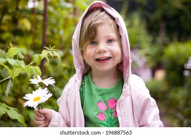 cute little blond girl with chamomiles in the summer garden