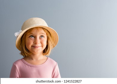 Cute little blond girl daydreaming with a happy smile looking up into the air letting her imagination run free over a blue background with copy space