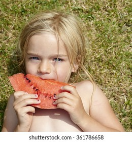 cute little blond girl eating water melon on the grass in summertime
