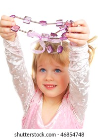 Cute little blond girl holding violet  beads up in hands isolated on the white background.