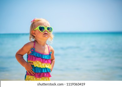 Cute little blond girl on the beach wearing sunglasses and stylish colorful swimsuit, child's fashion, summer vacation near the sea
