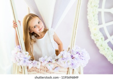 Cute little blond girl in a white dress standing in the beautiful decorative air balloon