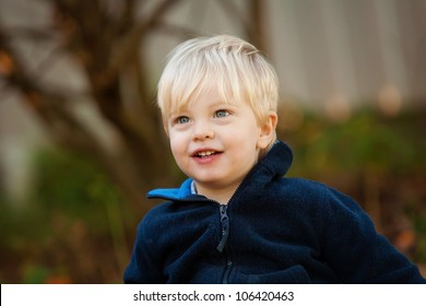 A cute little blonde 1 year old boy outdoors looking up.  He has a smile on his face.