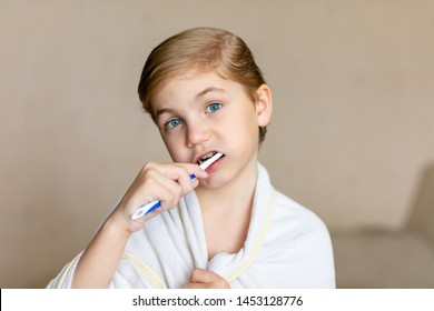 A cute little blonde boy with blue eyes brushing his teeth with a toothbrush. The concept of children's health, medicine.