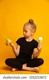 Cute little blonde girl in black leotard choosing between pear and sweet ice-cream on yellow background. Dieting and healthy eating concept
