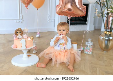 Cute little blonde girl celebrates first birthday at home in bright interior. 1 year baby girl in peach tutu with first birthday cake. Happy birthday card. First baby birthday, Smash cake concept.