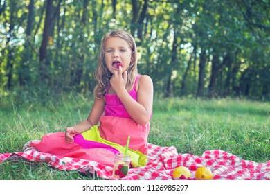 Cute little blonde girl eating ripe raspberries in the park