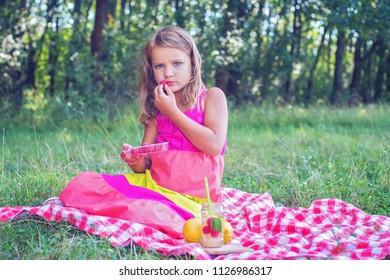Cute little blonde girl having a picnic and eating raspberries