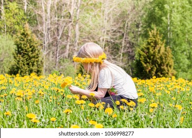 Cute little blonde girl on the meadow with yellow dandellion flowers in summer park.