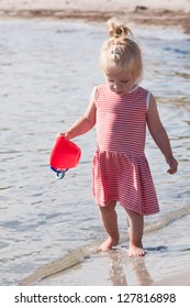 Cute little blonde girl playing at the seaside carrying a red bucket as she paddles at the edge of the surf on a sandy beach in summer sunshine