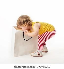 Cute little blonde girl reaching into a gift bag on a white background with surprised look on her face