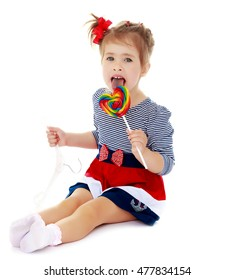 Cute little blonde girl with a red bow on her head, with pleasure licking colorful candy on a stick. Visible language which was painted in a candy color. Close-up.Isolated on a white background.