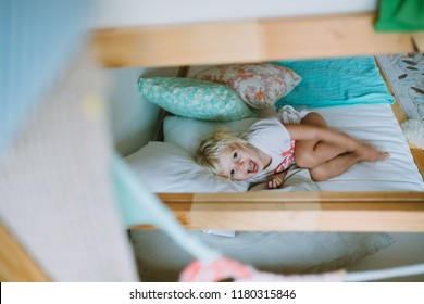 Cute little blonde girl smiling and lying in the bed covered with pillows