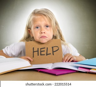 cute little blonde hair schoolgirl sad and frustrated holding help sign in stress with books and homework in children education concept isolated on grunge studio background