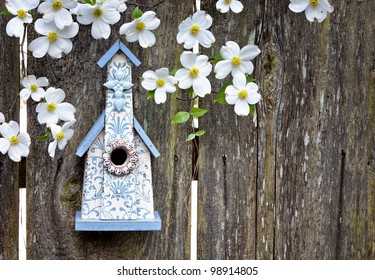 Cute little blue and white church birdhouse on rustic wooden fence with beautiful Dogwood blooms on them