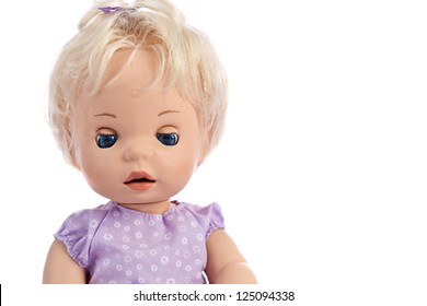 Cute little blue-eyed doll in purple dress on white background