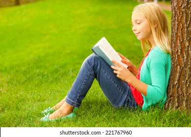 Cute little bookworm. Cute little blond hair girl reading book while sitting on green grass and leaning at the tree